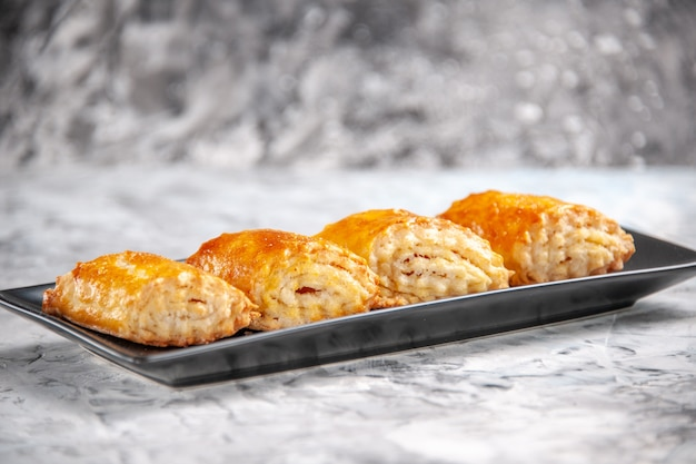 Vue de face de délicieuses pâtisseries sucrées à l'intérieur d'un moule à gâteau sur un gâteau à tarte à tarte de table blanc sucré