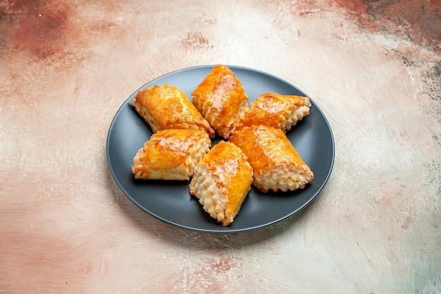 Vue de face de délicieuses pâtisseries sucrées à l'intérieur de la plaque sur une table blanche tarte gâteau pâtisserie sucrée
