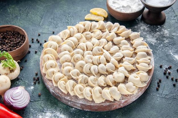 Vue de face de délicieuses petites boulettes avec de la farine sur une surface gris foncé