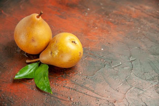 Vue de face de délicieuses poires sucrées sur fond sombre pulpe pomme photo arbre fruitier