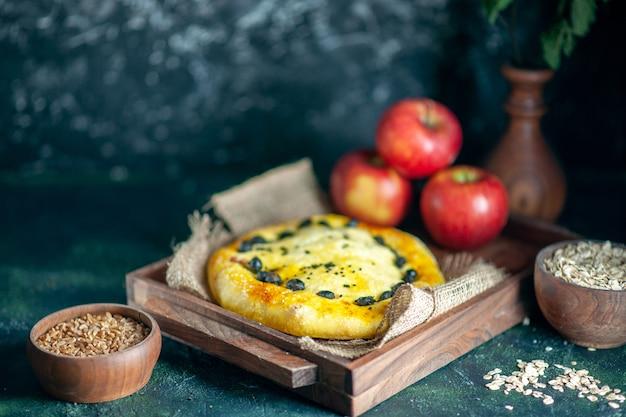 Vue de face de délicieuses pommes à pain sur une planche de bois rectangulaire, de l'avoine et des grains de blé dans des bols sur une surface sombre