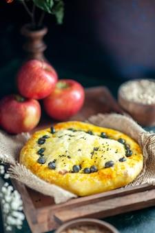 Vue de face de délicieuses pommes à pain sur une planche de bois rectangulaire sur une table