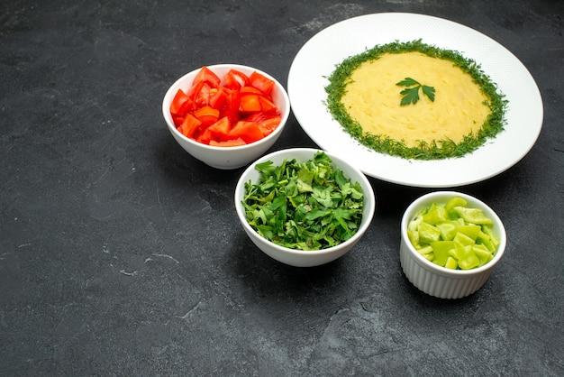 Vue de face de délicieuses pommes de terre en purée avec des légumes verts et des tranches de tomates fraîches sur un espace gris