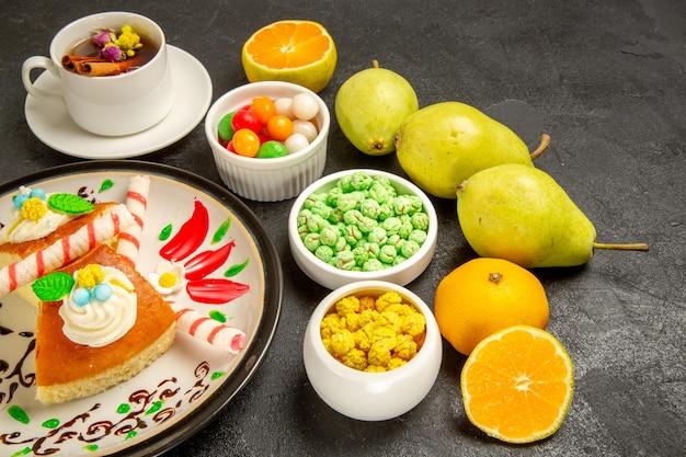 Vue de face de délicieuses tranches de gâteau à la crème avec une tasse de poires au thé et des bonbons sur un espace sombre