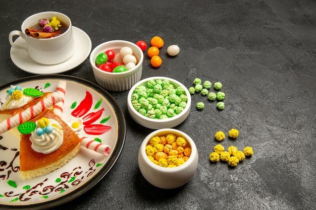 Vue de face de délicieuses tranches de gâteau à la crème avec une tasse de thé et des bonbons dans un espace sombre