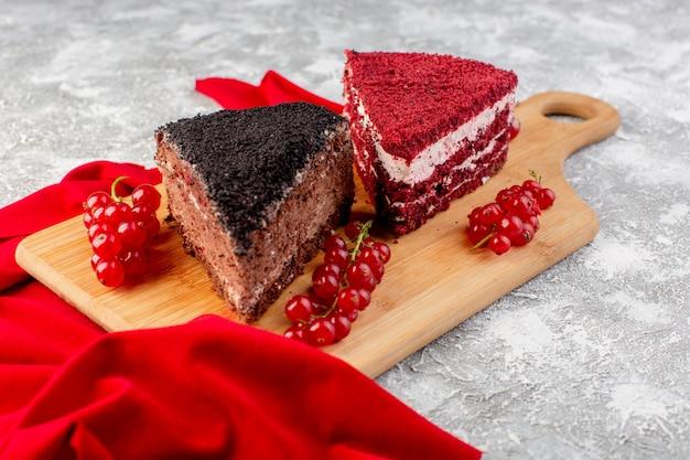 Vue de face de délicieuses tranches de gâteau avec du chocolat à la crème et des fruits avec du tissu rouge