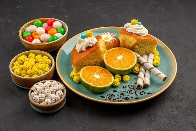 Vue de face de délicieuses tranches de gâteau avec des mandarines tranchées et des bonbons sur un espace sombre