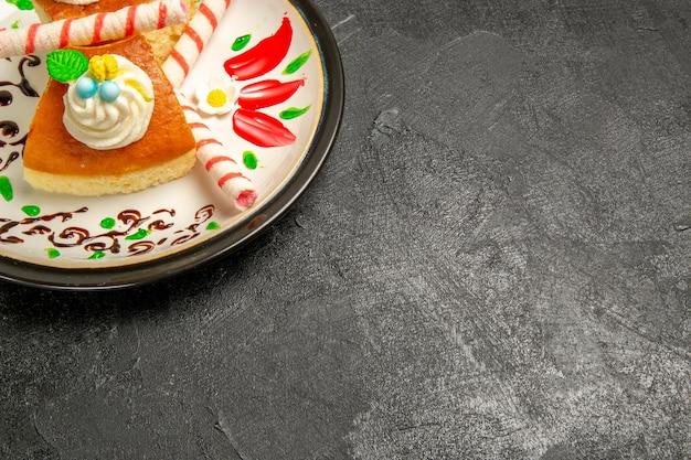 Vue de face de délicieuses tranches de gâteau sucré à la tarte à la crème à l'intérieur d'une assiette conçue sur l'espace sombre