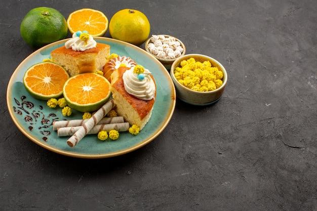 Vue de face de délicieuses tranches de tarte avec des bonbons et des mandarines fraîches sur l'espace sombre