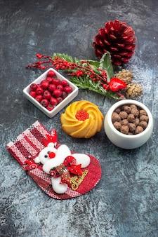 Vue de face d'un délicieux accessoire de décoration de biscuits, chaussette et cornell du père noël dans un bol de branches de sapin sur une surface sombre
