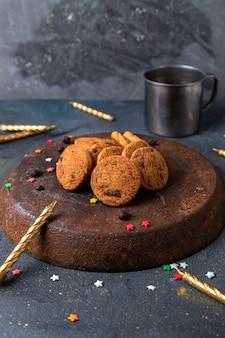 Vue de face de délicieux biscuits au chocolat avec des bougies sur la surface gris foncé