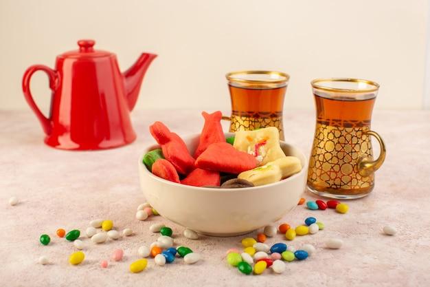 Vue de face de délicieux biscuits colorés différents formés à l'intérieur de la plaque avec des bonbons, des tasses de thé et une bouilloire rouge