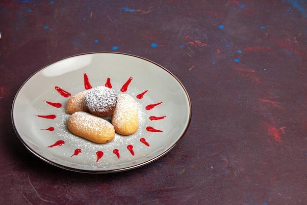 Vue de face de délicieux biscuits avec de la poudre de sucre et du glaçage rouge à l'intérieur de la plaque sur un espace sombre