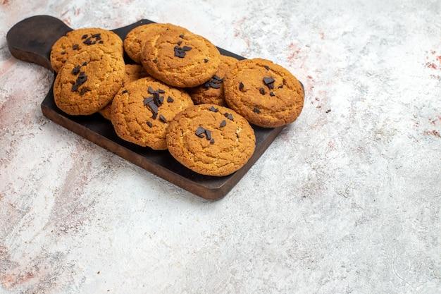 Vue de face de délicieux biscuits de sable bonbons parfaits pour une tasse de thé sur une surface blanche