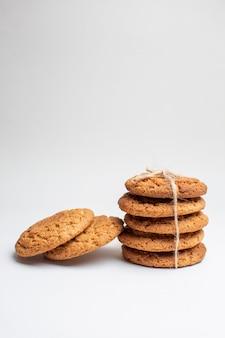 Vue de face de délicieux biscuits sucrés sur des biscuits blancs dessert thé photo gâteau sucre