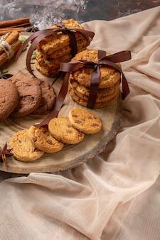Vue de face de délicieux biscuits sucrés avec une tasse de café sur la couleur de fond clair sucre de cacao gâteau au thé cookie tarte sucrée