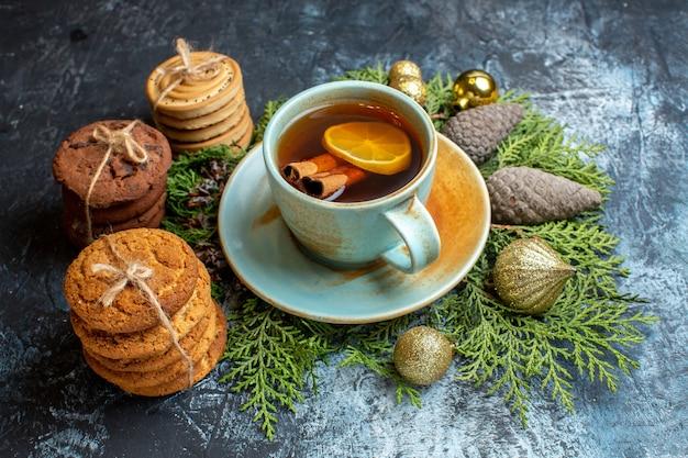 Vue de face de délicieux biscuits avec une tasse de thé sur la surface claire