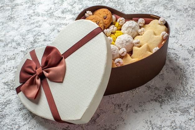 Vue de face de délicieux bonbons biscuits biscuits et bonbons à l'intérieur d'une boîte en forme de coeur