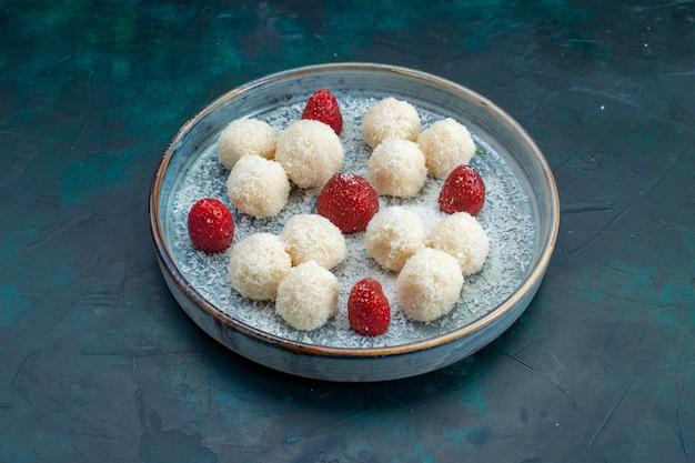 Vue de face de délicieux bonbons à la noix de coco avec des fraises