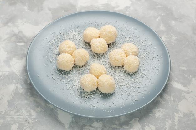 Vue de face de délicieux bonbons à la noix de coco à l'intérieur de la plaque bleue sur mur blanc