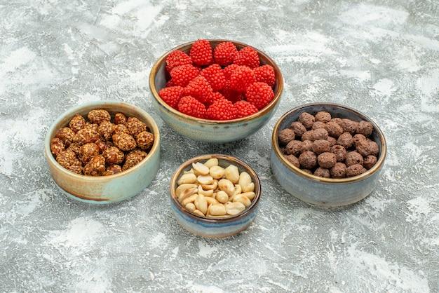 Vue de face de délicieux bonbons sucrés différents bonbons sur un espace blanc