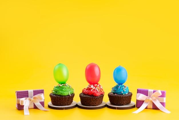 Une vue de face de délicieux brownies au chocolat à base de bonbons et de boules sur jaune, couleur biscuit gâteau bonbon