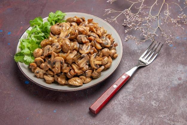 Vue de face de délicieux champignons cuits avec des verts sur un espace sombre