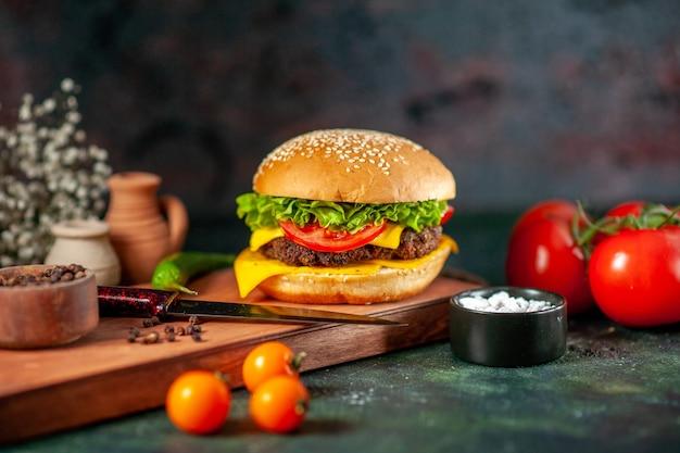 Vue de face délicieux cheeseburger sur fond sombre