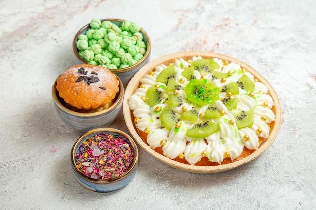 Vue de face délicieux dessert avec des kiwis tranchés et des bonbons sur un espace blanc