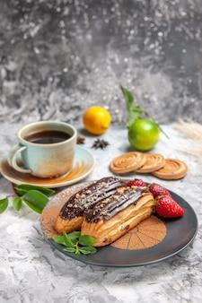 Vue de face de délicieux éclairs au chocolat avec du thé sur un gâteau de dessert aux biscuits de table blanche