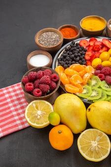 Vue de face de délicieux fruits tranchés à l'intérieur de la plaque avec des assaisonnements sur une surface sombre fruit exotique photo moelleux arbre mûr vie saine