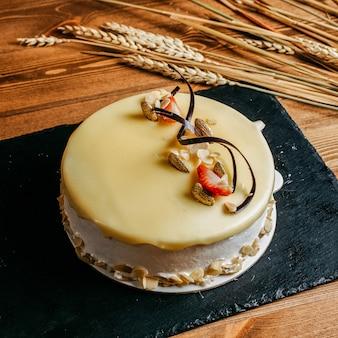 Une vue de face délicieux gâteau d'anniversaire décoré délicieux à l'intérieur de la plaque blanche d'anniversaire biscuit sucré sur le fond brun