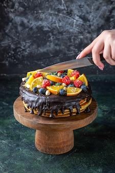 Vue de face délicieux gâteau au chocolat avec des fruits coupés par une femme sur un mur sombre