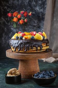 Vue de face délicieux gâteau au chocolat avec des fruits frais sur un mur sombre