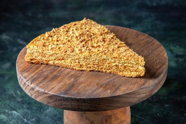 Vue de face de délicieux gâteau au miel tranche de celui-ci sur une surface sombre de planche de bois ronde