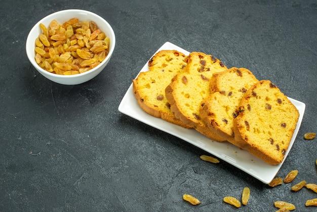 Vue de face délicieux gâteau aux raisins secs avec des raisins secs frais sur une surface sombre gâteau sucré biscuit thé tarte thé