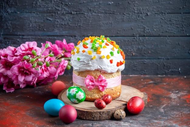 Vue de face délicieux gâteau à la crème avec des fruits secs pour pâques sur fond sombre couleur ethnique pâques coloré vacances ornées