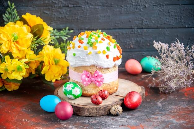 Vue de face délicieux gâteau à la crème avec des fruits secs pour pâques avec des œufs colorés sur fond sombre couleur ethnique pâques vacances ornées