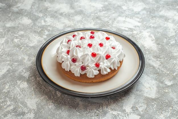 Vue de face d'un délicieux gâteau crémeux décoré de fruits sur fond de glace