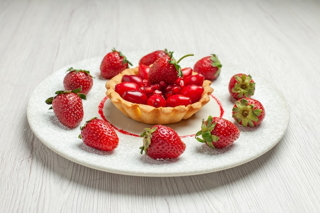 Vue de face délicieux gâteau avec des fruits frais à l'intérieur de la plaque sur le dessert gâteau aux fruits bureau blanc