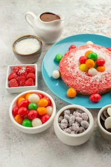 Vue de face délicieux gâteau rose avec des bonbons colorés sur fond blanc couleur dessert cookie bonbons gâteau arc-en-ciel