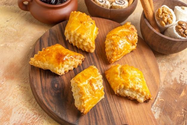 Vue de face de délicieux gâteaux aux noix avec des confitures sur une surface en bois