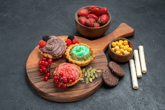 Vue de face de délicieux gâteaux crémeux aux fruits sur fond sombre