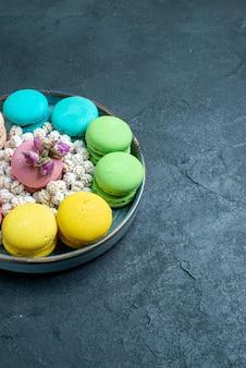 Vue de face de délicieux macarons français avec des bonbons à l'intérieur du plateau sur un bureau sombre