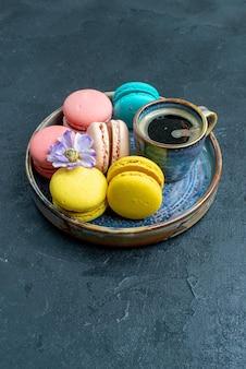 Vue de face de délicieux macarons français avec du café dans un espace sombre