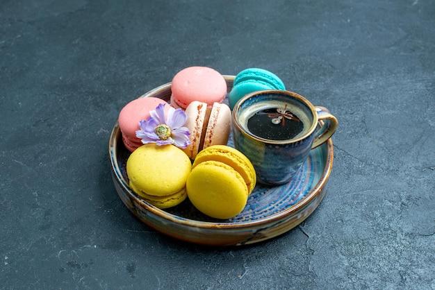 Vue de face de délicieux macarons français avec une tasse de café dans un espace sombre