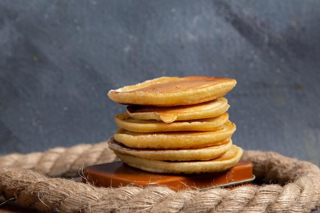 Vue de face de délicieux muffins avec des cordes sur la surface grise