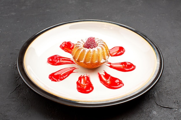 Vue de face délicieux petit gâteau avec glaçage rouge à l'intérieur de la plaque sur fond sombre thé biscuit sucré tarte au sucre cookie