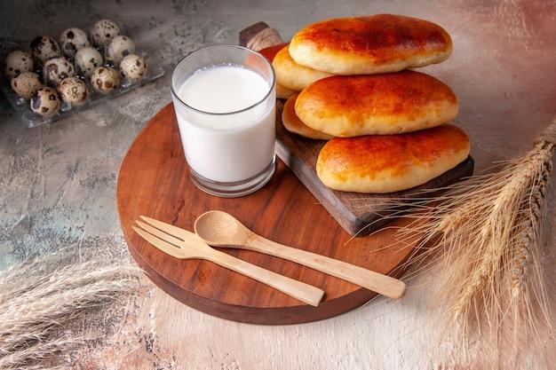 Vue de face de délicieux petits pains cuits au four avec un verre de lait