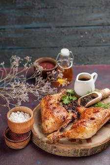 Vue de face délicieux poulet frit avec différents assaisonnements sur un bureau sombre